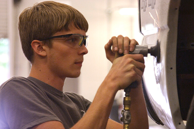 Student using a sander on a car to prepare it for painting