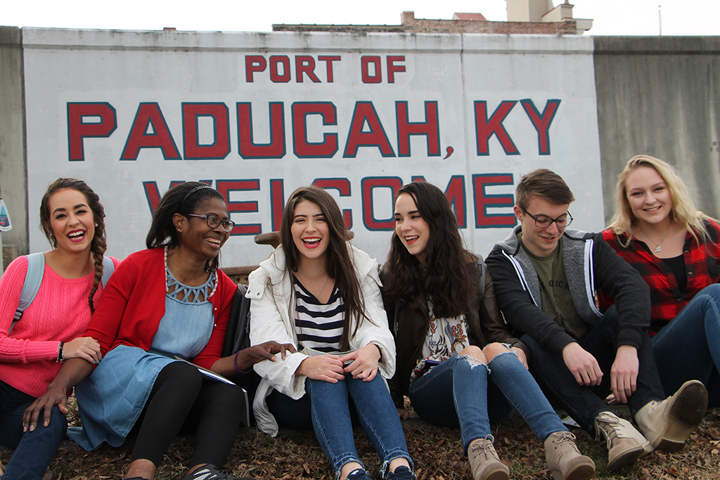 people on wall in front of paducah, KY port sign