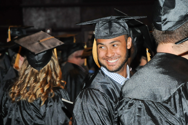 student in cap and gown smiling at his family